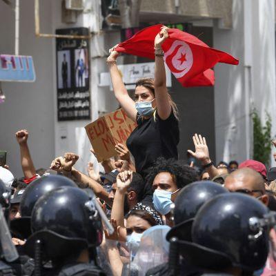 Kvinna med munskydd och Tunisiens flagga i händerna.