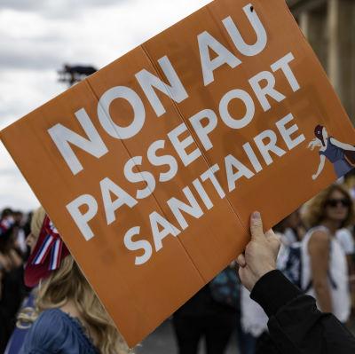 """Bild på en orange skylt där det står """"nej till hälsopass"""" skrivet på franska. Bakom syns en folkmassa och Eiffeltornet."""