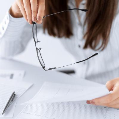 Kvinna bläddrar i papper med glasögonen i handen.