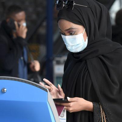 En passagerare iförd ansiktsskydd checkar in digitalt på Helsingfors-Vanda flygplats.