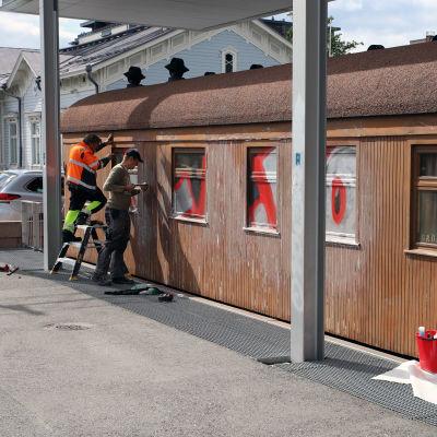 Rakennusmiehiä korjaamassa graffitilla töhrittyä Mannerheimin salonkivaunua.