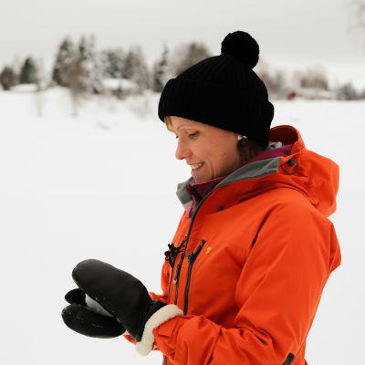 Kaisa Sali lumisessa maisemassa. Kaisalla on punainen kuoritakki ja musta pipo. Käsissään hän muotoilee lumipalloa. Taustalla on jäätynyt joen uoma, vastarannalla on metsää ja mökkejä. Keskellä jokea on sininen kyltti, josta ei saa kuvassa selvää.