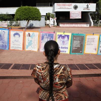 Kvinna tittar på bilder av de 43 studeranden som försvann i delstaten Guerrero i Mexico.