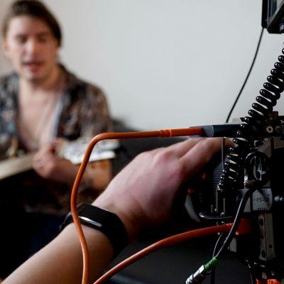 Musikern André Linman spelar gitarr och sjunger framför videokamera.