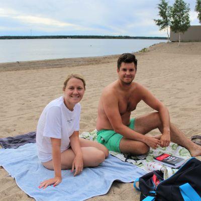 En kvinna och en man sitter på var sin handduk på en sandstrand.