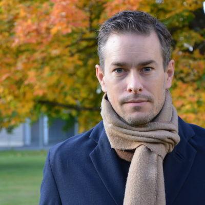 Kim Strandberg, en vit man med halsduk står framför ett träd i höstskrud.
