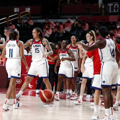 En rad men amerikanska spelare i vita speltröjor klappar om varandra och ger high-fives.