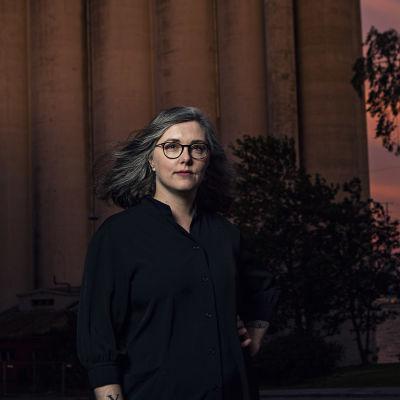 På bilden syns författaren Elin Willows iklädd en svart skjorta och svarta glasöogon. Bakgrunden är mörk och orangerosa av solnedgången.