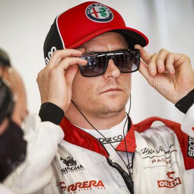 Kimi Räikkönen tar på sig solglasögonen.