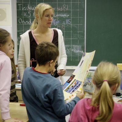 Lärare och några barn i ett klassrum.