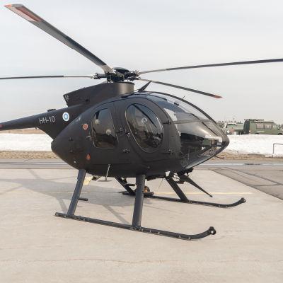 Mustaksi maalattu MD500-kevythelikopteri Utin lentokentällä.
