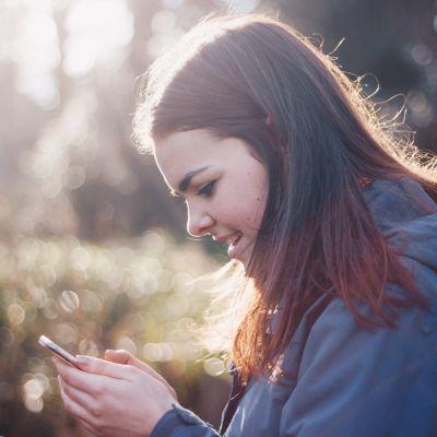 Flicka ser på sin smarttelefon ute i skogen.