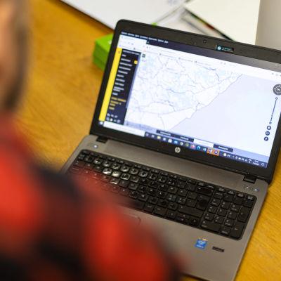 Etelä-Karjalan kalatalouskeskuksen toiminnanjohtaja Joonas Häkkinen katsoo entisen toiminnanjohtajan kannettavalta tietokoneelta karttaa.