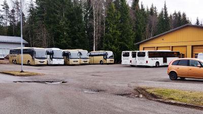 Flera bussar på en parkeringsplats.