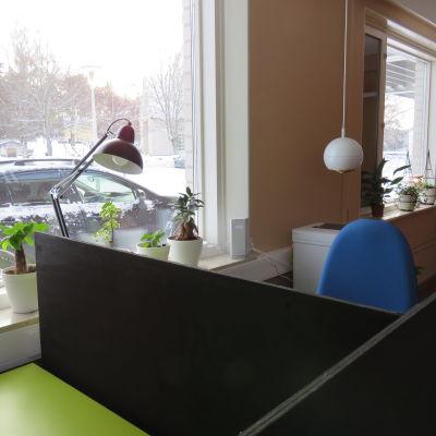 Ett litet kontor för distansjobb. Kontorsstol, arbetsbord, en printer i bakgrunden. Fönster med snölandskap ute.