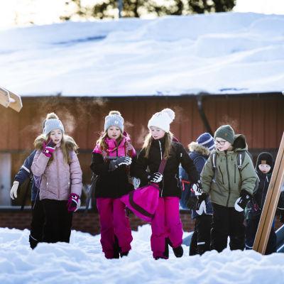 Barn i rad på solig skolgård med snö.