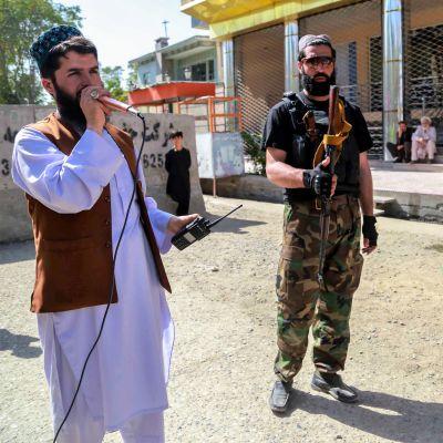 Valkoasuinen parrakas mies mikrofoniin, radiopuhelin toisessa kädessään, Vieressä seisoo kaksi tummiin asuihin pukeutunutta miestä rynnäkkökiväärien kanssa.