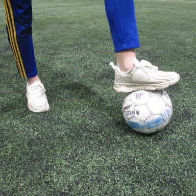 Spelare står med foten på en fotboll
