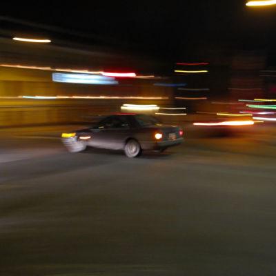 En bil kör i en stad när det är mörkt. Konturerna på bilden är suddiga.