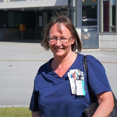 Kvinna i sjukhuskläder står framför en betongbyggnad.