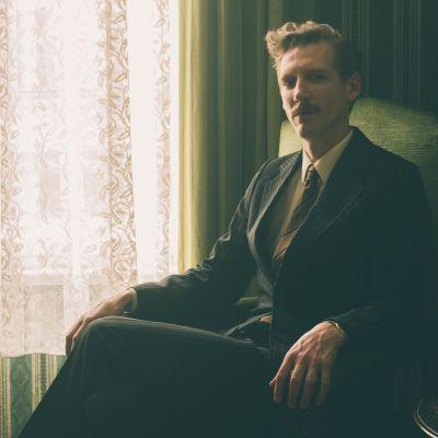 Touko Laaksonen (Pekka Strang) sitter i en fåtölj och ser rakt in i kameran.