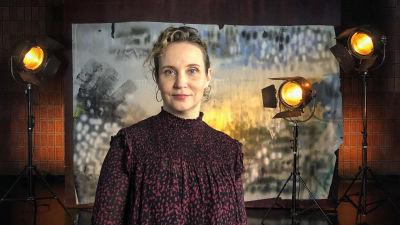 Kirsikka Saari seisoo studiossa taustalavasteen ja studiolamppujen edessä. Kuva otettu lyhytvideosarjaan Me elokuvantekijät.