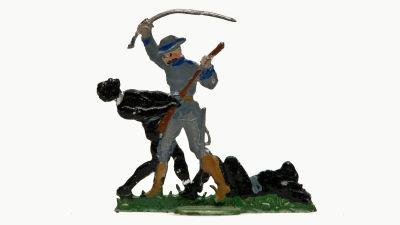 En tennfigur föreställer en vit man som höjer ett svärd ovanför en mörkhyad man. I gräset bredvid ligger en till mörkhyad person.