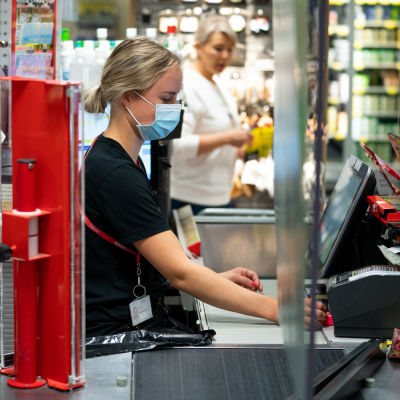 Salen myyjä palvelee asiakasta maski päässään.