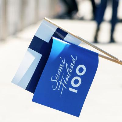 Finlands flagga och Finland 100 flagga i en medborgares hand, 2017