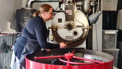 En kvinna håller i en kaffeskopa intill en kafferost.