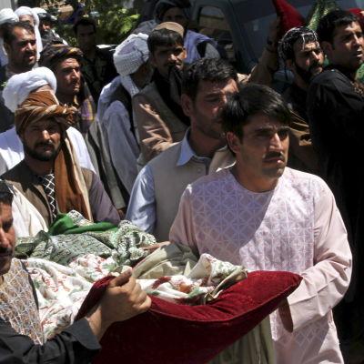 Anhöriga bär på kroppen till en av de civila som dödades i en NATO-bombning 5 augusti 2014.