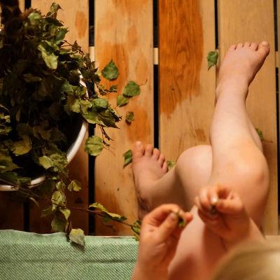 Tyttö istuu saunan lauteilla vihtojen kanssa.