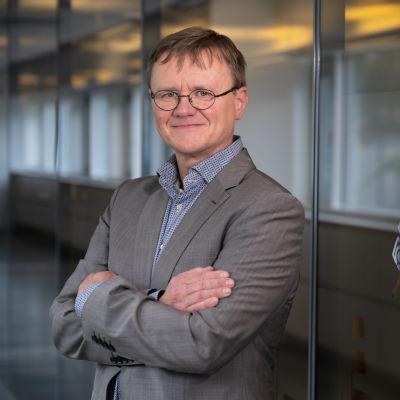 Timo Koivurova seisoo kädet puuskassa Ylen käytävällä.