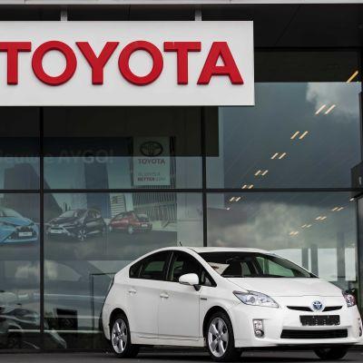 Vit Toyota-bil framför bilaffär.