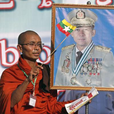 En buddhistisk munk viftade med en flagga och ett porträtt av överbefälhavare Min Aung Hlaing under en demonstration till stöd för militären i Rangoon den 14 oktober 2018.