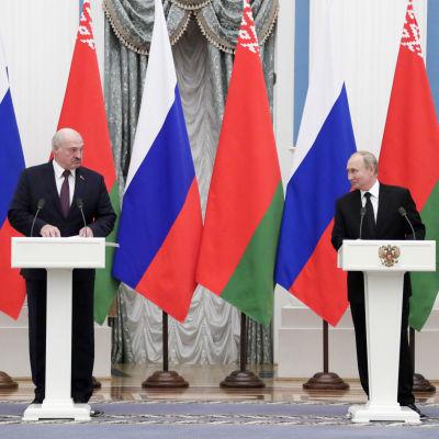 Aleksandr Lukasjenko och Vladimit Putin står vid respektive podium och håller presskonferens framför en rad av belarusiska och ryska flaggor.