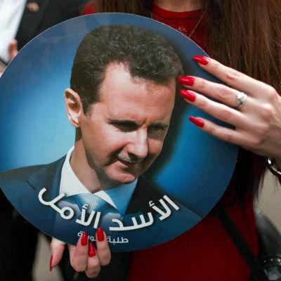 En kvinna som håller i ett porträtt av Syriens president Bashir al-Assad.