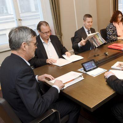 Kostymklädda män, och en kvinna, sitter runt ett bord.