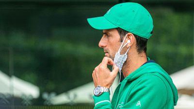 Novak Djokovic med munskyddet hängande under hakan.