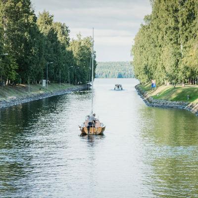 Segelbåt på väg bortåt längsmed kanal, längre bort skymtas mynningen till en sjö.