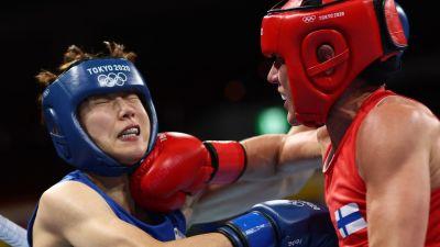 Mira Potkonen i röd tröja delar ut ett slag mot en motståndare i blått.