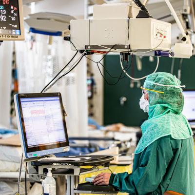 En sjukskötare jobbar vid en monitor på intensivvårdsavdelningen för coronapatienter.