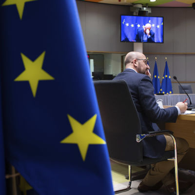 Europeiska rådets ordförande Charles Michel. Bilden domineras av en stor EU-flagga i förgrunden. I bakgrunden syns en videoskärm.
