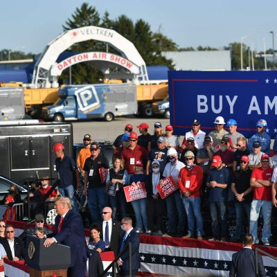 Donald Traump på massmöte utomhus, banderoll om att köpa amerikanskt