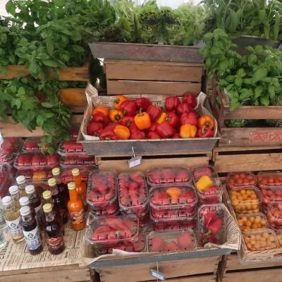 Tomater, paprika och gröna örter i gammaldags trälådor prydligt uppradade i ett marknadsstånd.