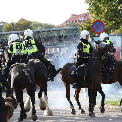 Poliser på polishästar rider på Göteborgs gator under en stor demonstration. Rök av en rökbomb syns på vilden.