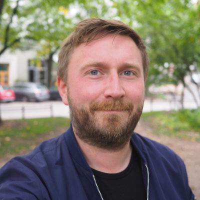 Man i blå skjorta står i en park i Helsingfors och ser mot kameran.