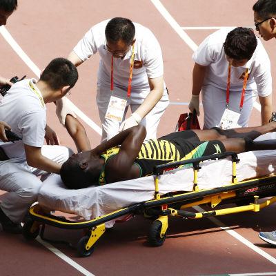 Javon Francis bärs ut på bår, VM i Peking 2015.