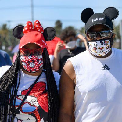 En kvinna och en man i ansiktsskydd poserar för kameran. Kvinnan bär Mickey Mouse-öron och håller upp sin telefon med ena handen. Mannen har också på sig Mickey Mouse-öron