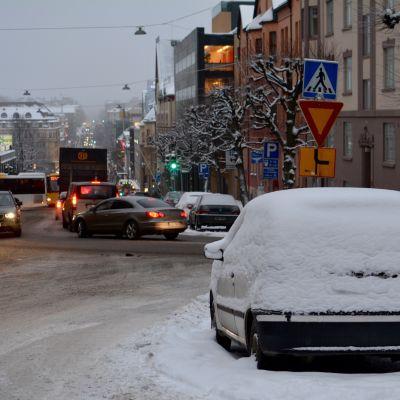 Trafik och en snöig bil i Puolalabacken i Åbo